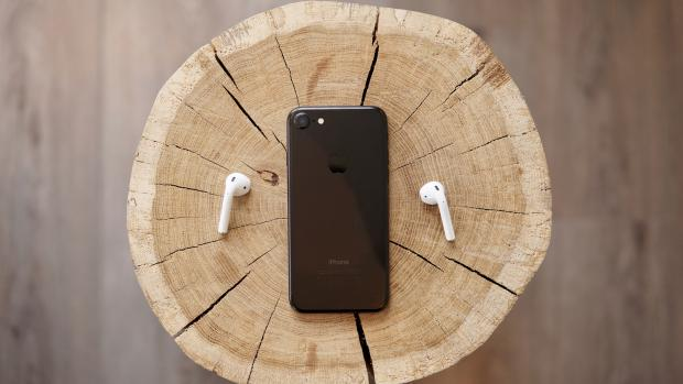iphone 7 and earpods on a wooden stump