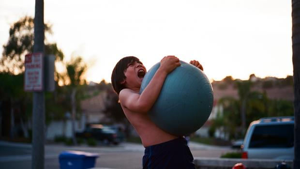 frustrated boy carrying blue ball